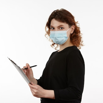 Jeune fille avec un masque de protection sur le visage avec un cahier et un stylo dans les mains.