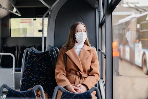Une jeune fille masquée utilise seule les transports en commun, lors d'une pandémie. protection et prévention covid 19.