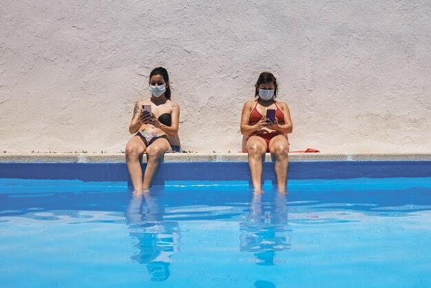 Jeune fille avec des masques se faire bronzer dans la piscine à l'aide de son téléphone portable