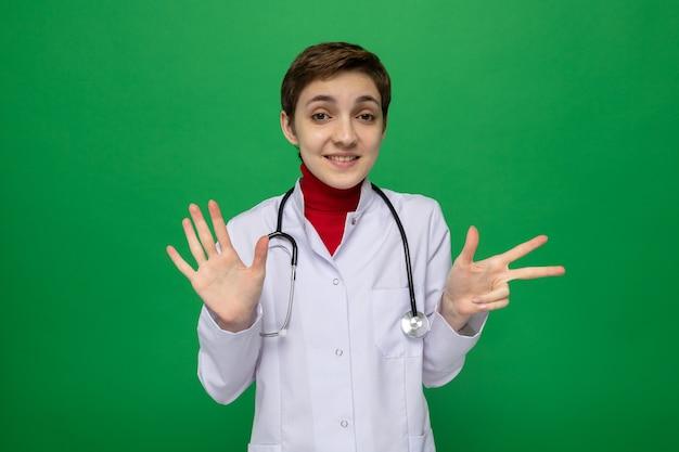 Jeune fille médecin en blouse blanche avec stéthoscope autour du cou souriant montrant le numéro cinq avec les doigts pointés avec l'index sur le côté debout sur le vert