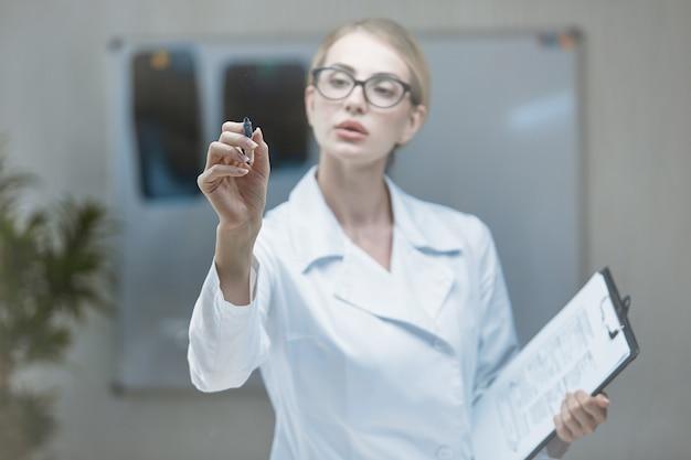 Une jeune fille médecin élabore un plan sur un écran de verre avec un marqueur