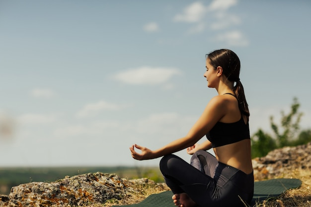 Jeune fille médite dans la position du lotus au sommet des montagnes.