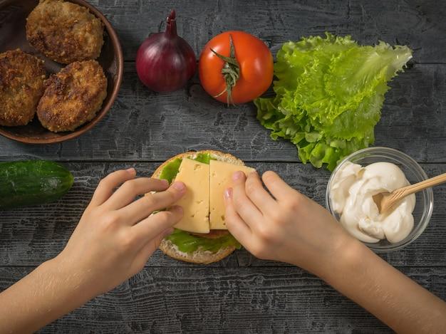 La jeune fille met le fromage dans la fabrication de hamburger