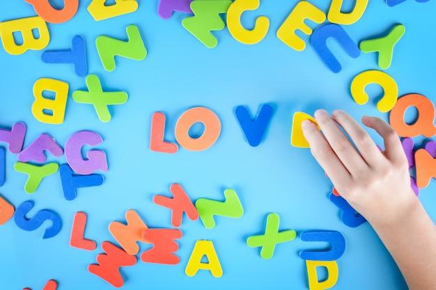 La jeune fille met le mot amour hors des lettres colorées. beau fond.