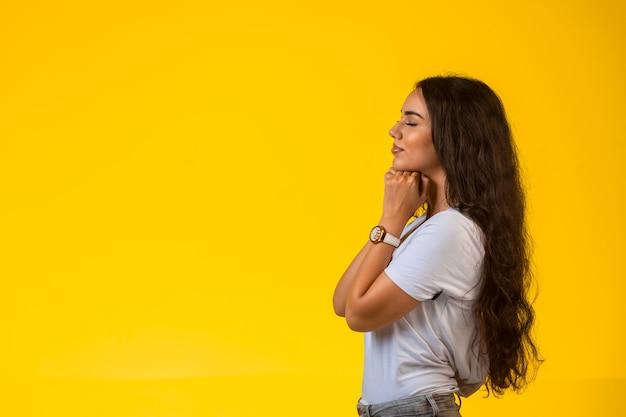 Jeune fille met ses mains sous son menton et prie, vue de profil.