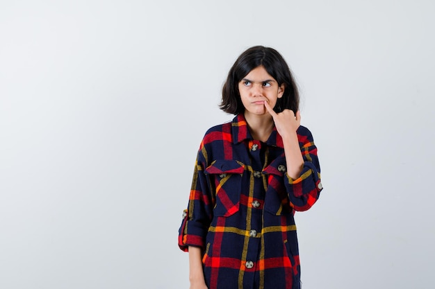 Jeune fille mettant l'index sur la bouche, regardant loin en chemise à carreaux et l'air mignon, vue de face.