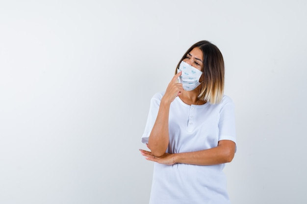 Jeune fille mettant l'index sur la bouche, tenant la main sous le coude en t-shirt blanc et masque et regardant pensif, vue de face.