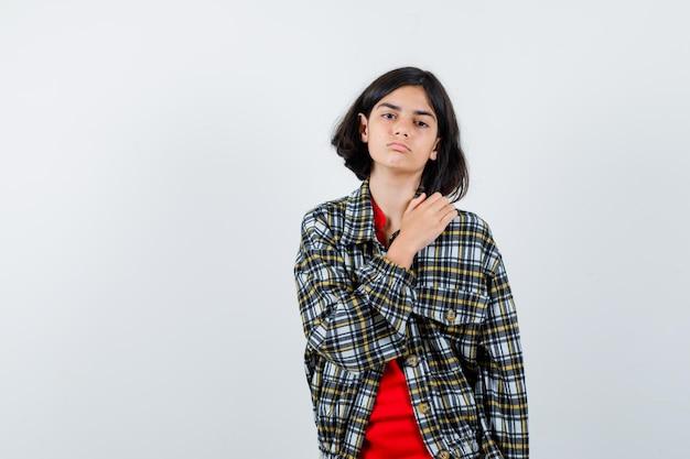 Jeune fille mettant la main sur l'épaule en chemise à carreaux et t-shirt rouge et l'air sérieux. vue de face.
