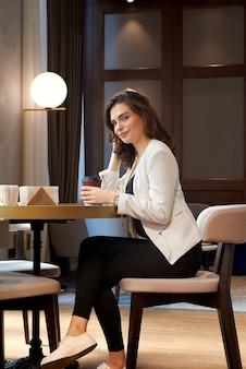 Jeune fille mignonne, buvant du café au café