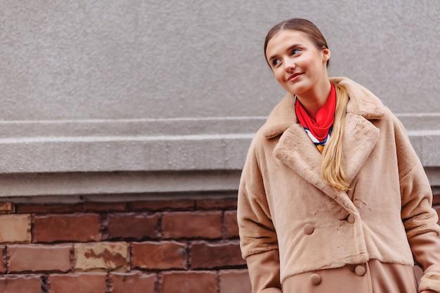 Jeune fille mignonne élégante dans un manteau de fourrure se promener dans la ville près des maisons en bois et des murs en pierre