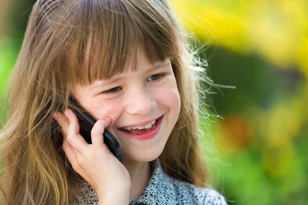 Jeune fille mignonne enfant parler au téléphone cellulaire à l'extérieur. les enfants et la technologie moderne, la communication.