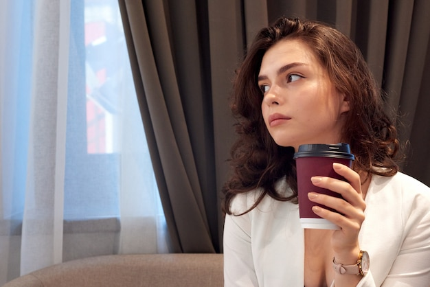 Jeune fille mignonne réfléchie, buvant du café dans un café