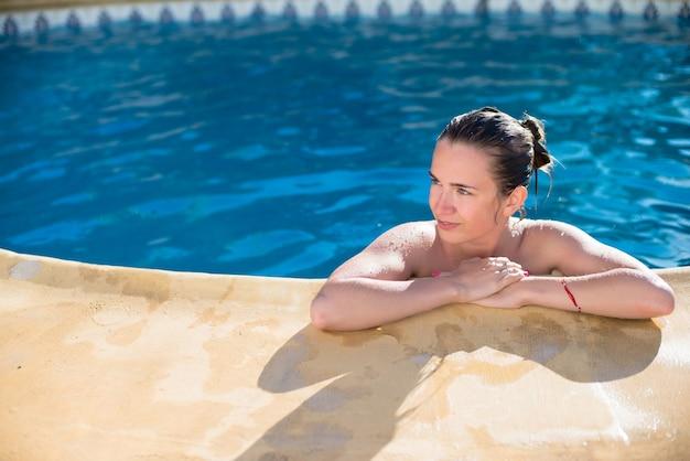 Jeune fille mignonne se détend à la piscine