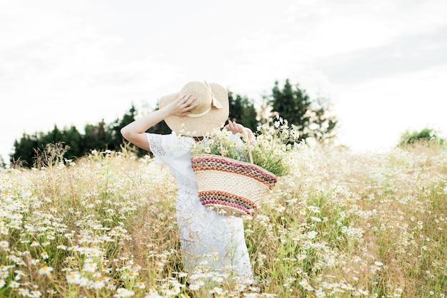 Jeune fille mignonne, tendre rêveuse amoureuse, dans un champ de marguerites. en robe et chapeau en osier. été chaud et ensoleillé, coucher de soleil dans le village. concept de liberté et style de vie