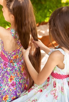 Jeune fille mignonne tressant la soeur aînée au parc