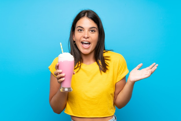 Jeune fille avec un milkshake à la fraise sur un mur isolé avec une expression faciale choquée