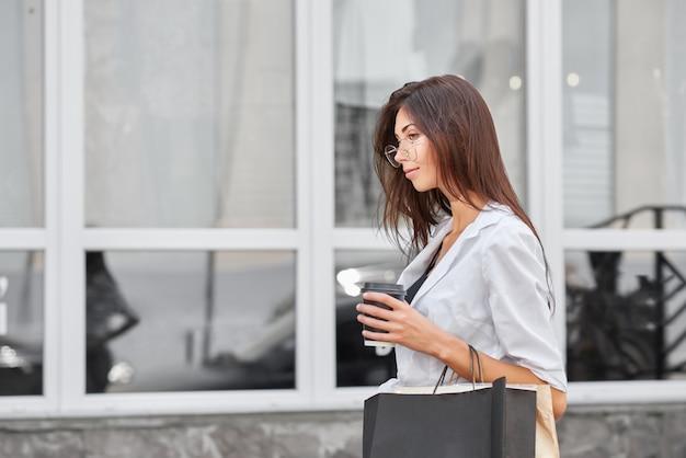 Jeune fille mince aux longs cheveux bruns sortant du magasin transportant des sacs.
