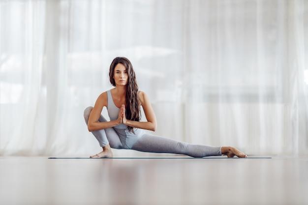 Jeune fille mince coupe attrayante aux cheveux longs en position de fente latérale. intérieur du studio de yoga.