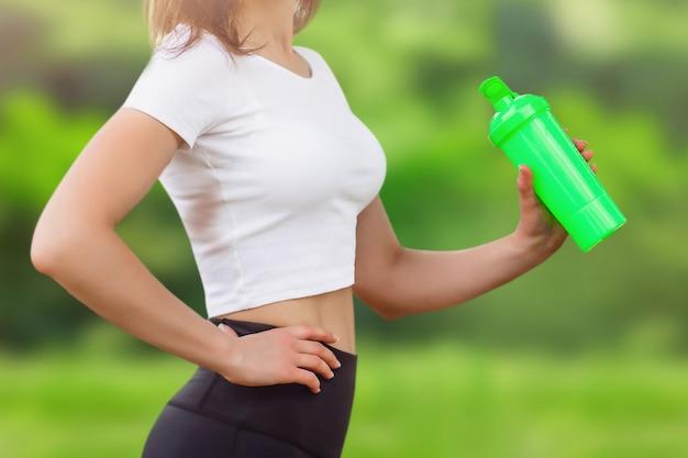 Jeune fille mince dans un t-shirt blanc tenant une bouteille de sport à la main.