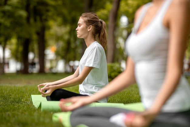Une jeune fille mince est assise dans la position du lotus, les yeux fermés, faisant des exercices avec d'autres filles sur l'herbe verte dans le parc par une chaude journée. .