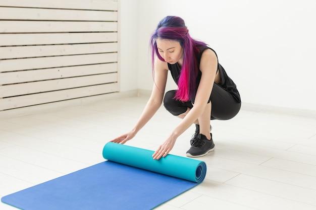 Jeune fille mince hipster aux cheveux colorés plie un tapis de sport de gymnastique et après les cours dans la salle de gym. concept de yoga et de pilates.