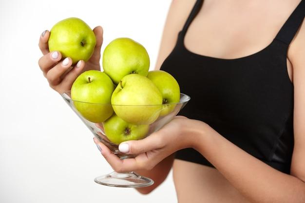 Une jeune fille mince tient un bol avec des pommes vertes dans ses mains sur un fond blanc.