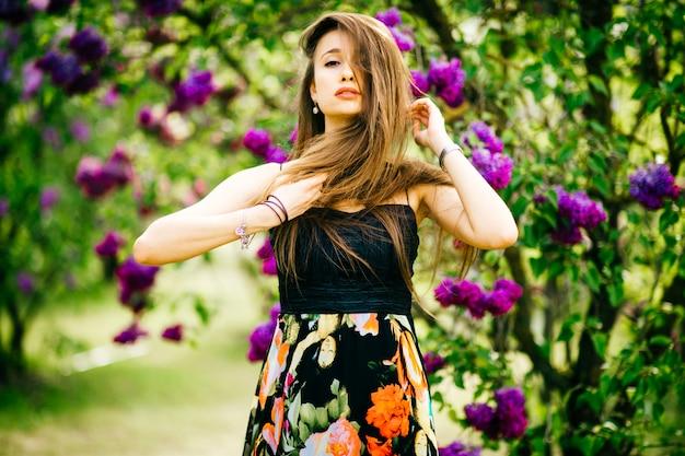 Jeune fille à la mode brunnette posant pour la caméra dans le parc fleuri de printemps.