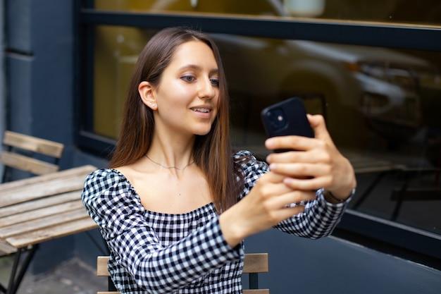 Une jeune fille à la mode fait un portrait de selfie au téléphone alors qu'elle est assise à une table dans un café en plein air. le blogueur communique avec ses abonnés