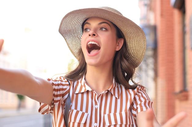 Une jeune fille à la mode fait un selfie des mains avec un téléphone dans la rue de la ville d'été.