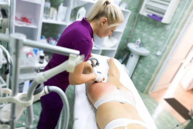 Une jeune fille modèle en culotte se trouve sur la procédure de massage sous vide le maître effectue l'étude des zones à problèmes