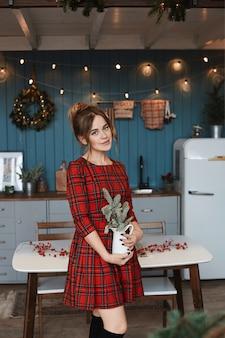 Jeune fille modèle en robe rouge à carreaux posant avec des décorations de noël dans la cuisine