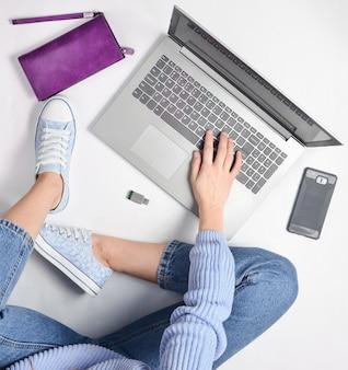 Une jeune fille moderne est assise sur un sol blanc et utilise un ordinateur portable