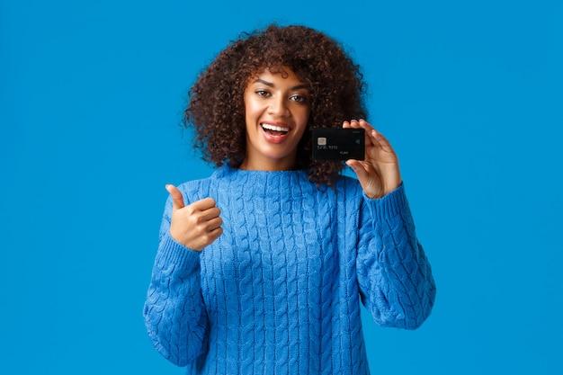 Une jeune fille moderne satisfaite a obtenu un compte bancaire, ouvert un dépôt, en utilisant un service de cashback