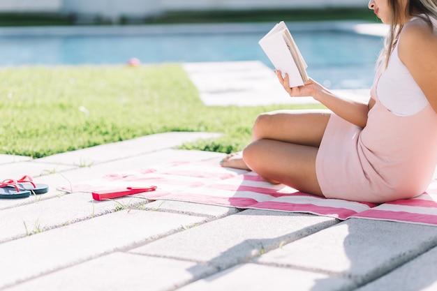 Jeune fille de moitié du corps lisant un livre un jour ensoleillé
