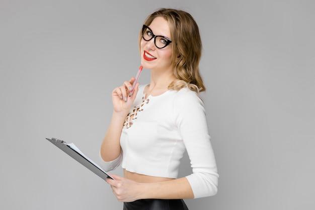 Une jeune fille à moitié réveillée porte des lunettes avec un stylo et un tableau d'enregistrement.