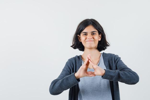 Jeune fille montrant une forme de triangle avec les mains en t-shirt gris clair et sweat à capuche zippé gris foncé et à mignon,