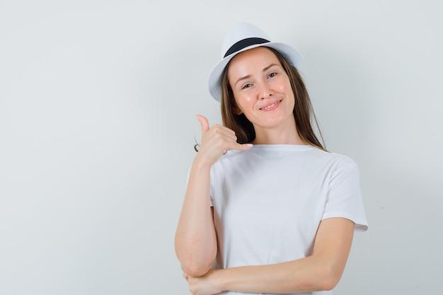 Jeune fille montrant le geste du téléphone en t-shirt blanc, chapeau et à la recherche utile. vue de face.
