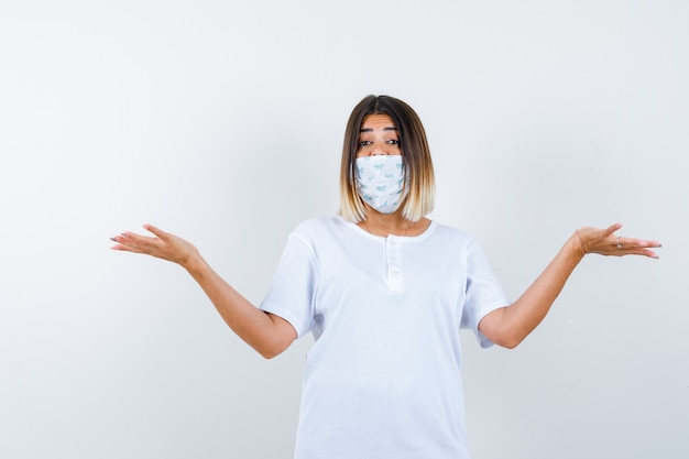 Jeune fille montrant un geste impuissant en t-shirt blanc et masque et à la perplexe, vue de face.