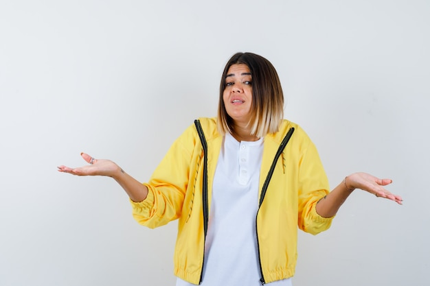 Jeune fille montrant un geste impuissant en t-shirt blanc, veste jaune et à la perplexité, vue de face.