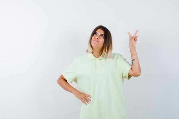 Jeune fille montrant le geste de paix, tenant la main sur la taille en t-shirt et regardant pensif, vue de face.