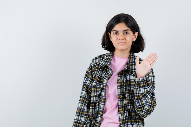 Jeune fille montrant un panneau d'arrêt en chemise à carreaux et t-shirt rose et jolie vue de face.
