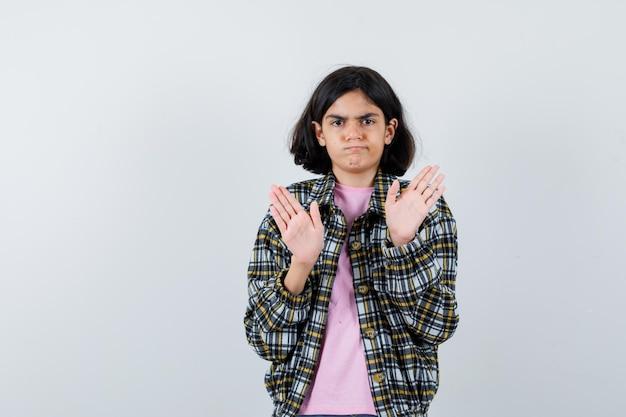 Jeune fille montrant des panneaux d'arrêt en chemise à carreaux et t-shirt rose et l'air sérieux. vue de face.