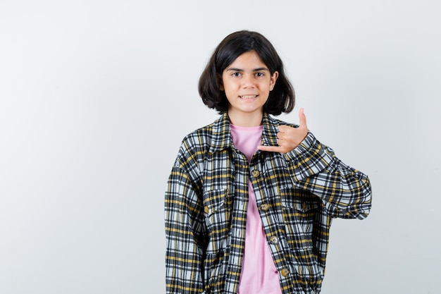 Jeune fille montrant les pouces vers le haut dans une chemise à carreaux et un t-shirt rose et à la jolie vue de face.