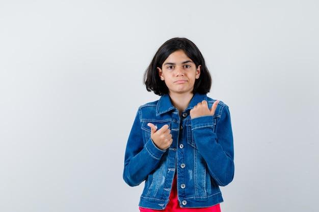 Jeune fille montrant les pouces vers le haut avec les deux mains en t-shirt rouge et veste en jean et à la mignonne