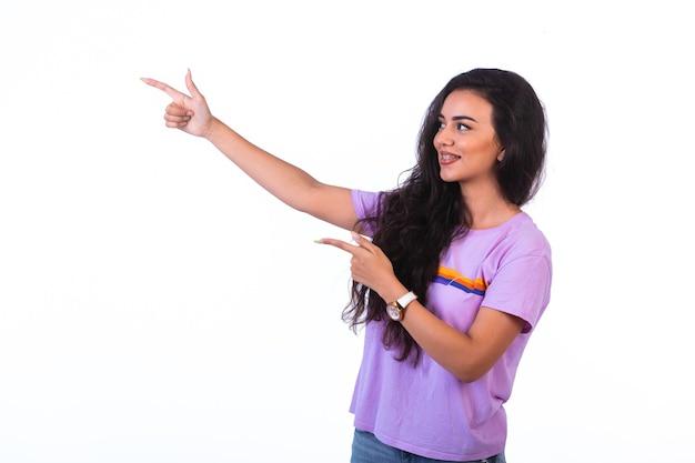 Jeune fille montrant quelque chose et faisant une présentation sur fond blanc