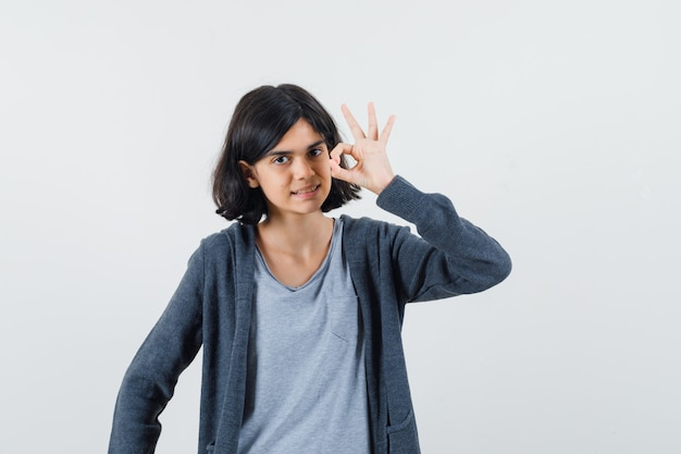 Jeune fille montrant le signe ok en t-shirt gris clair et sweat à capuche zippé gris foncé et à la recherche de mignon.