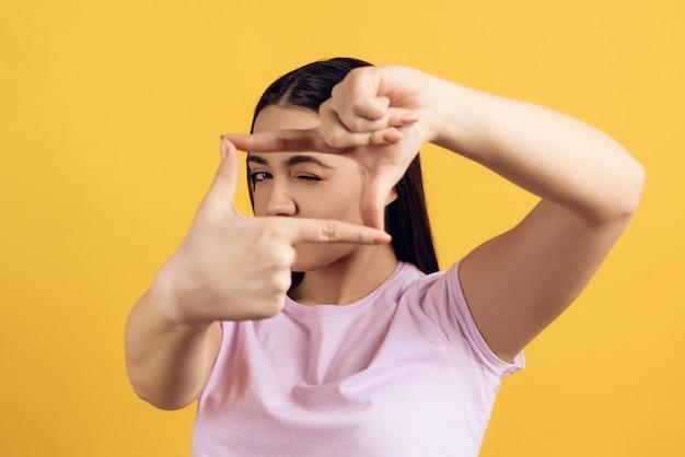 Jeune fille montre le geste de prendre des photos.