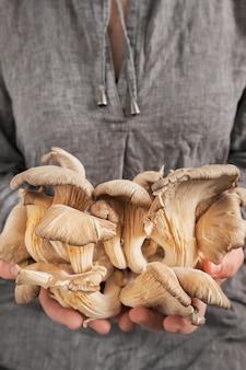 La jeune fille montre une récolte fraîche de pleurotes dans ses mains