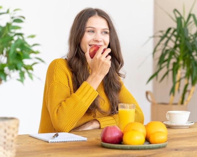 Jeune fille mordant la pomme rouge, souriant. belle femme aux cheveux longs en pull jaune vif, manger des fruits pour la désintoxication
