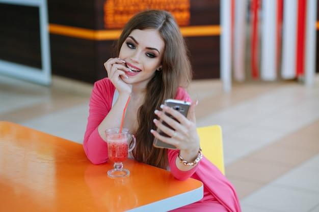 Jeune fille de mordre son doigt en regardant son téléphone intelligent